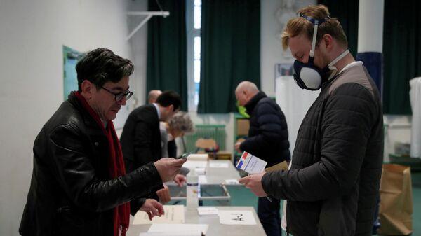 Избиратели на участке во время первого тура выборов мэра в Париже, Франция