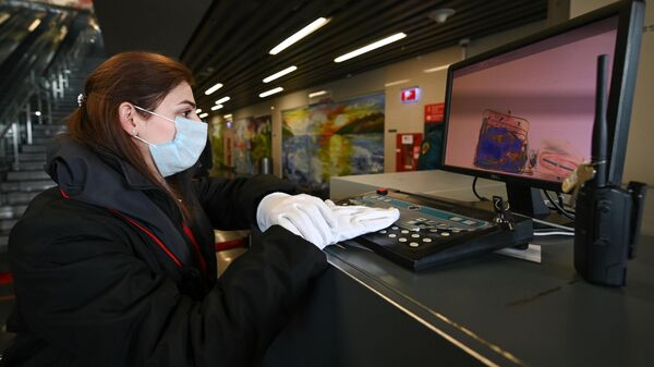 Сотрудница ОАО Российские железные дороги досматривает багаж пассажиров на железнодорожном вокзале Адлера