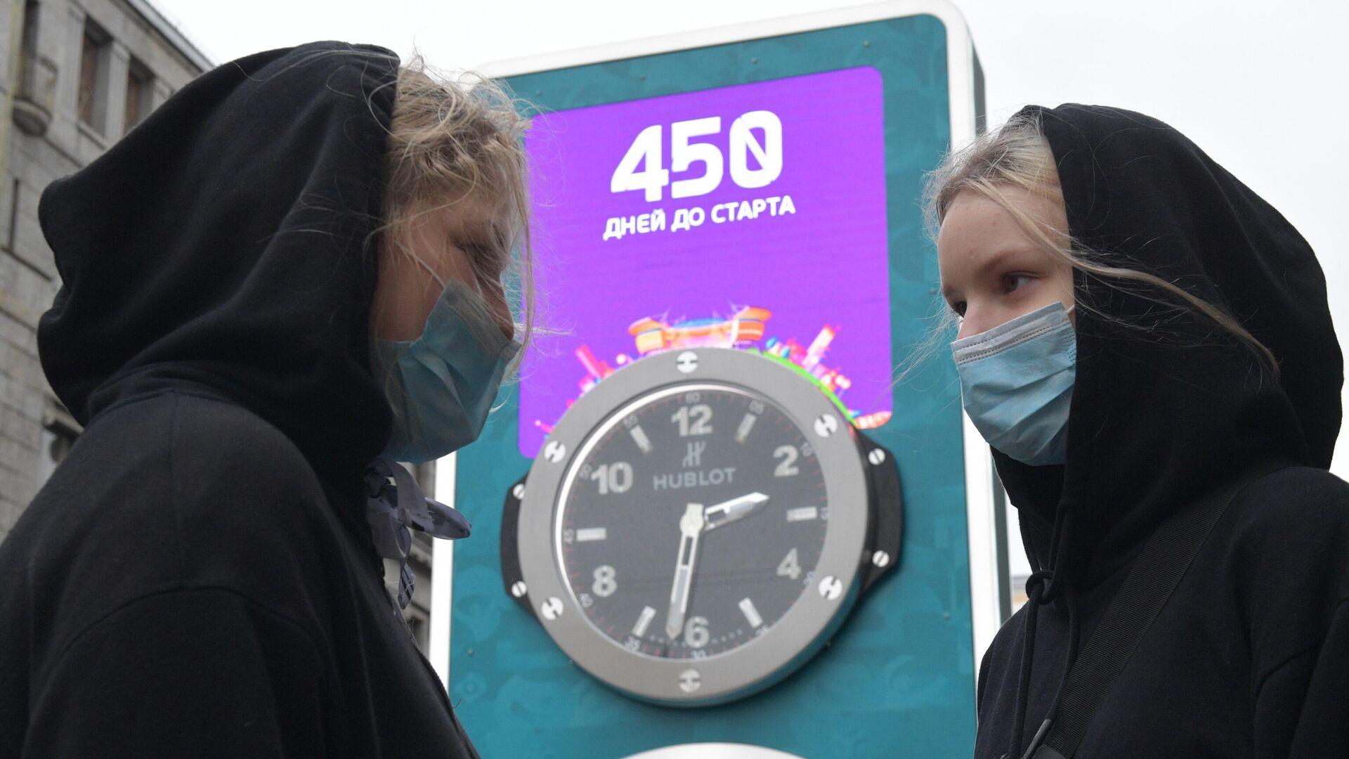 Девушки в медицинских масках рядом с часами обратного отсчета времени до старта чемпионата Европы по футболу - РИА Новости, 1920, 20.03.2020