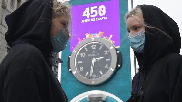 Девушки в медицинских масках рядом с часами обратного отсчета времени до старта чемпионата Европы по футболу