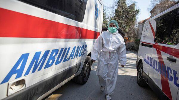 Медицинский работник в защитном костюме в инфекционной больнице в Белграде