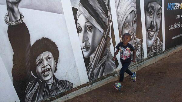 Мальчик проходит мимо портрета Винни Манделы во время празднования дня окончания апартеида в Южной Африке