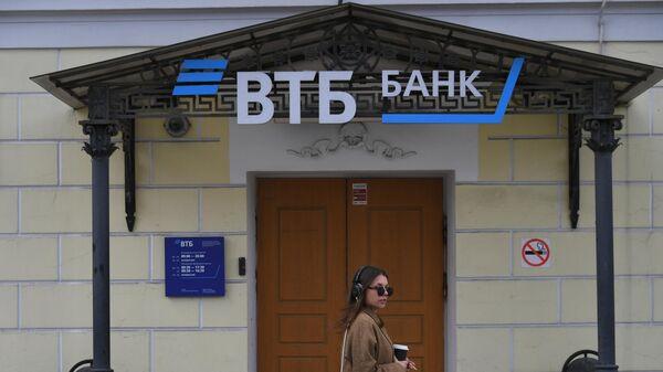 Девушка проходит мимо отделения банка ВТБ на одной из улиц в Москве