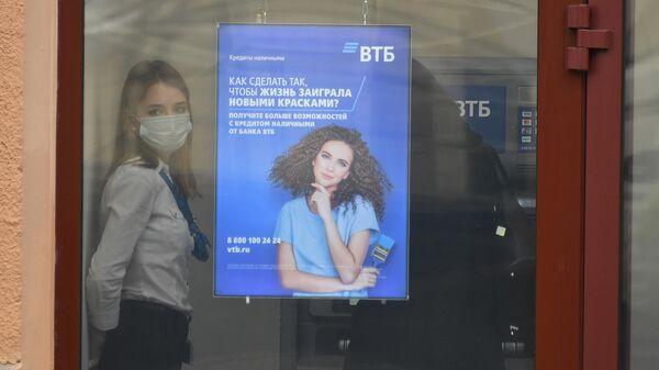 Сотрудница в защитной маске в отделении банка ВТБ на одной из улиц в Москве