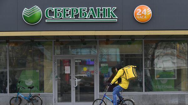 Курьер сервиса доставки Яндекс.Еда у отделения ПАО Сбербанк на одной из улиц в Москве