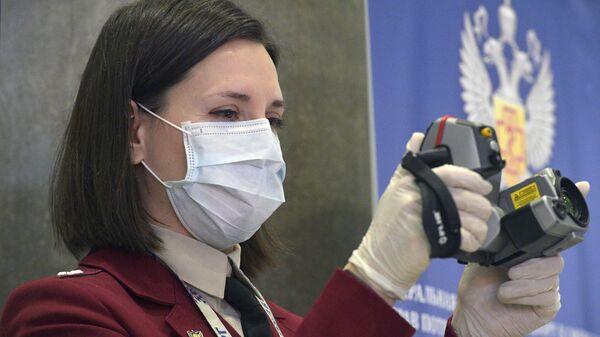 Сотрудник Роспотребнадзора с прибором для измерения температуры прибывающих в аэропорт Пулково