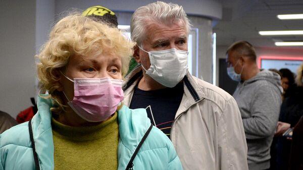 Пассажиры в защитных масках в национальном аэропорту Минск