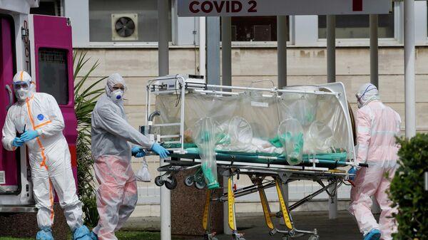 Медицинские работники несут пациента, доставленного в больницу Columbus Covid 2 в Риме
