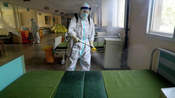 Работник в защитном костюме дезинфицирует больницу № 7 города Ухань