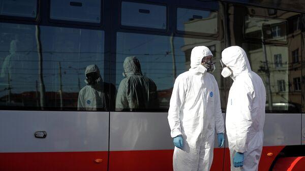 Рабочие в защитных костюмах готовятся во время дезинфекции трамваев в Праге