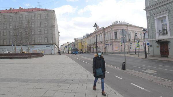 Девушка в защитной маске улице Большая Никитская в Москве