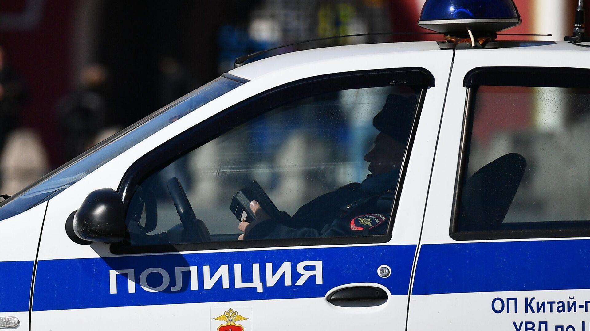 Сотрудник правоохранительных органов в полицейской машине в центре Москвы - РИА Новости, 1920, 16.06.2021