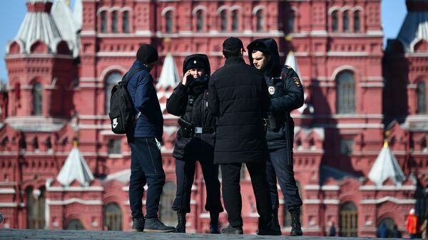 Сотрудник правоохранительных органов проверяют документы у прохожих на Красной площади в Москве