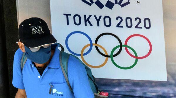 Прохожий возле баннера с символикой Олимпийских игр в Токио