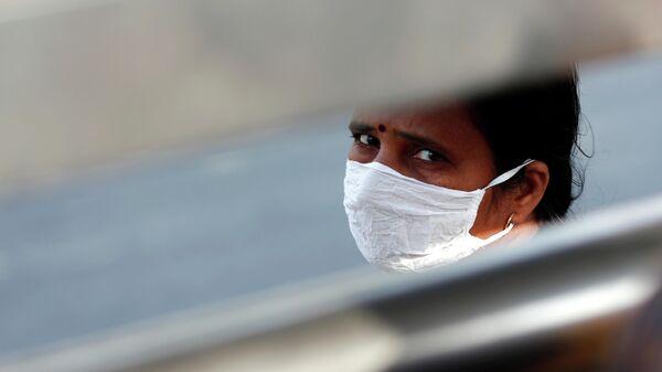 Женщина в защитной маске в Нью-Дели