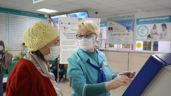 Сотрудница поликлиники  помогает посетительнице получить талон к врачу