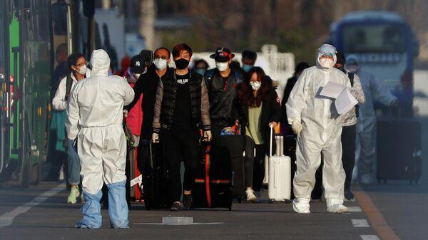 Сотрудники в защитных костюмах сопровождают пассажиров возле международного аэропорта Шоуду в Пекине