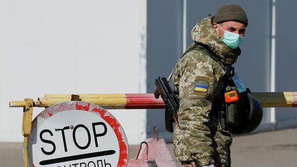 Украинский пограничник в защитной маске на контрольно-пропускном пункте в Майорске, Украина. 17 марта 2020 года