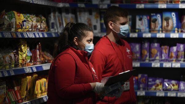 Волонтёры покупают в магазине продукты для пенсионера