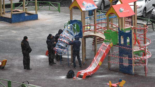 Сотрудники коммунальной службы огораживают детскую площадку в одном из дворов Мытищ
