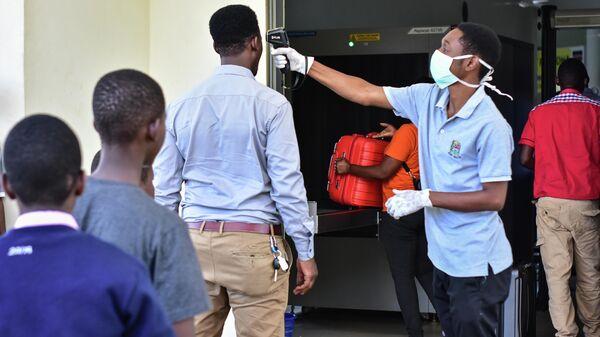 Рабочий проверяет температуру в Танзании