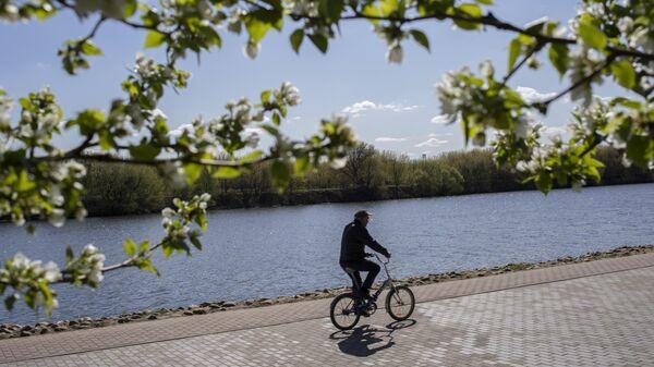 Мужчина едет на велосипеде в музее-заповеднике Коломенское