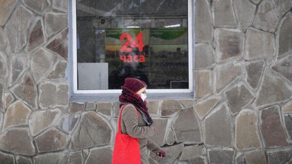 Девушка в медицинской маске около магазина в городе Щелково