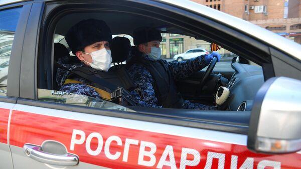 Сотрудники Росгвардии в медицинских масках во время проверки соблюдения домашнего режима на одной из улиц в Москве