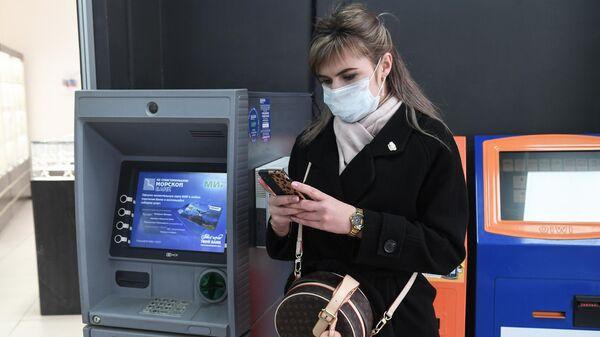 Девушка стоит возле банкомата в Симферополе
