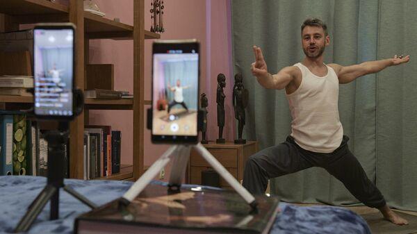 Инструктор по йоге Сергей Баранов проводит трансляцию и видеозапись урока йоги у себя дома в Санкт-Петербурге