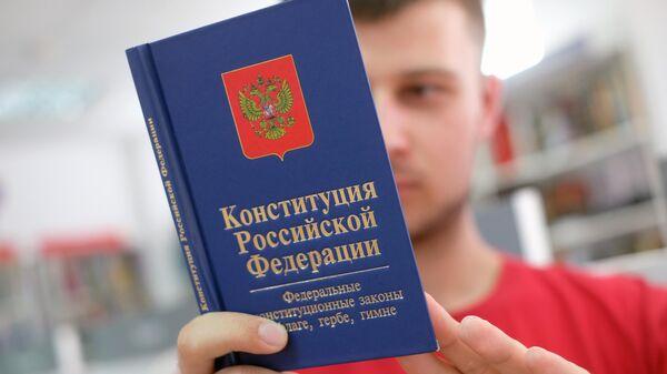 Молодой человек держит книгу конституции Российской Федерации
