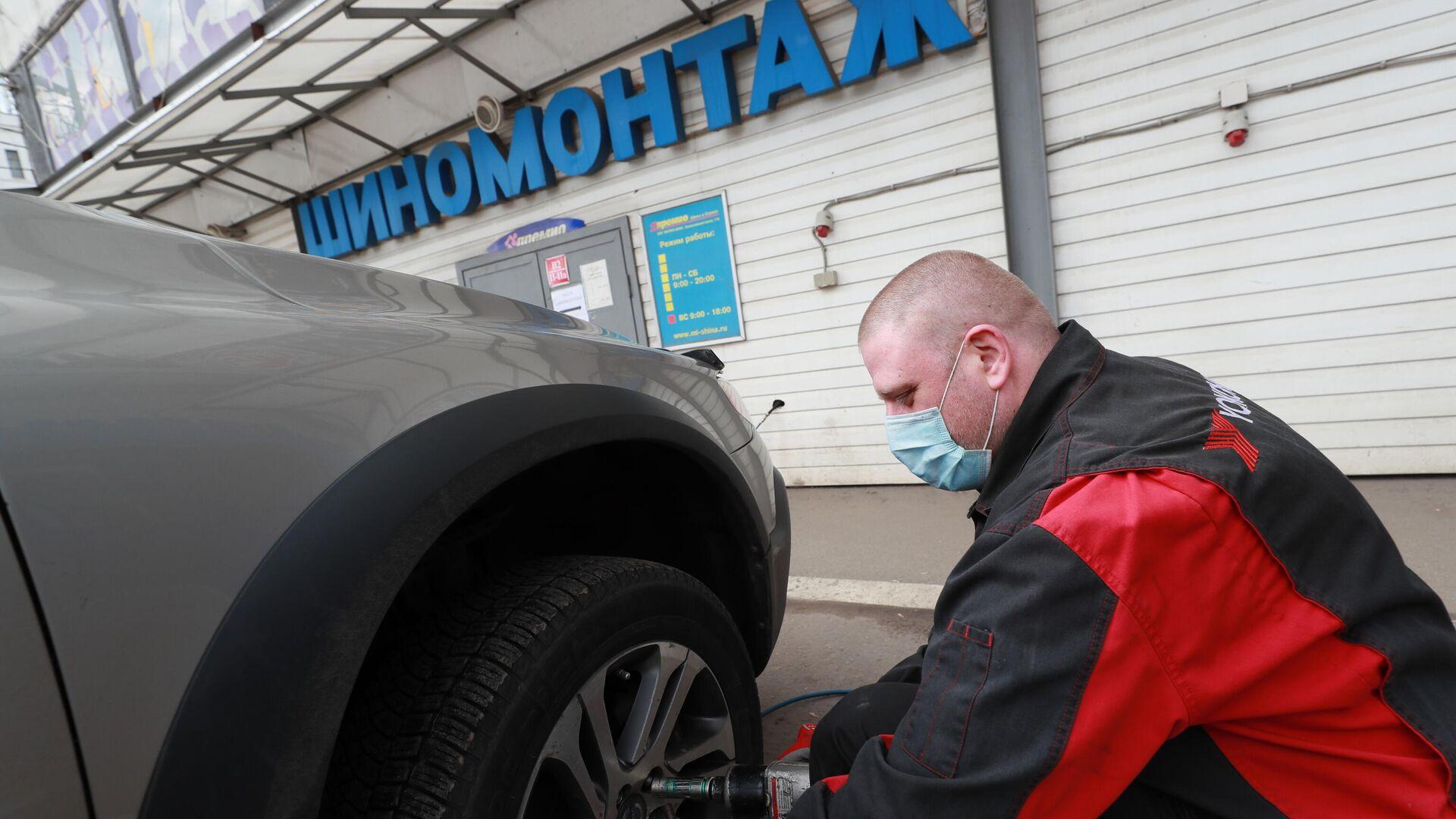 Работник шиномонтажа на Волоколамском шоссе в Москве - РИА Новости, 1920, 28.03.2021