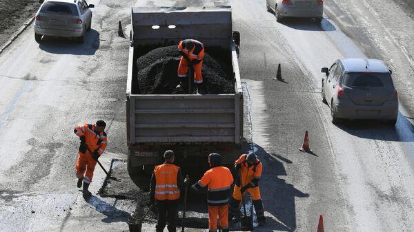 Рабочие проводят текущий весенний ремонт дорожного покрытия в Новосибирске