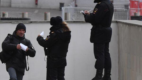 Сотрудники полиции проверяет документы у мужчины в Москве