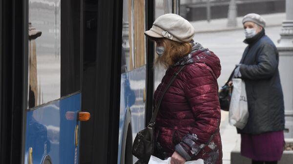 Женщины в медицинских масках у городского автобуса в Москве