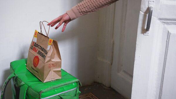 Жительница Москвы, соблюдающая режим самоизоляции из-за распространения коронавирусной инфекции, забирает заказ из Макдональдса, доставленный курьером службы Delivery Club к двери ее квартиры