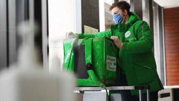 Курьер службы Delivery Club протирает сумку, перед тем как взять заказ в Макдональдсе