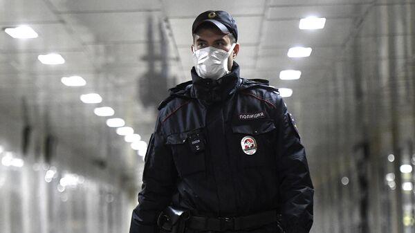 Сотрудник полиции в защитной маске на станции метро Тверская Московского метрополитена
