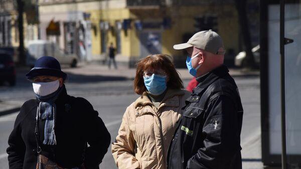 Прохожие в защитных масках на улице во Львове