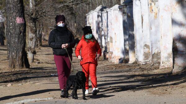 Женщина с ребенком в защитных масках выгуливают собаку на одной из улиц в Чите