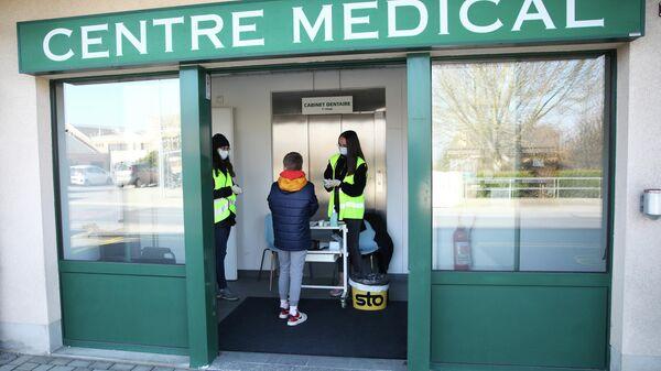 Волонтеры в защитных масках у входа в медицинский центр в Швейцарии