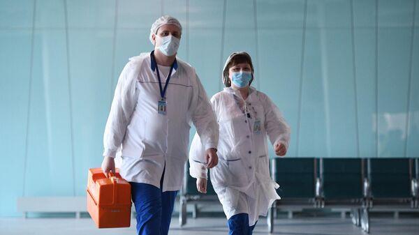 Врачи в масках перед встречей пассажиров рейса 5702 Бангкок - Новосибирск