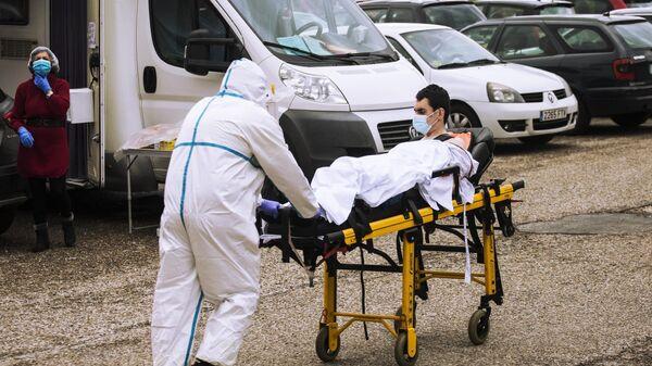 Медицинский работник доставляет пациента на каталке в приемное отделение госпиталя Северо Очоа в Мадриде