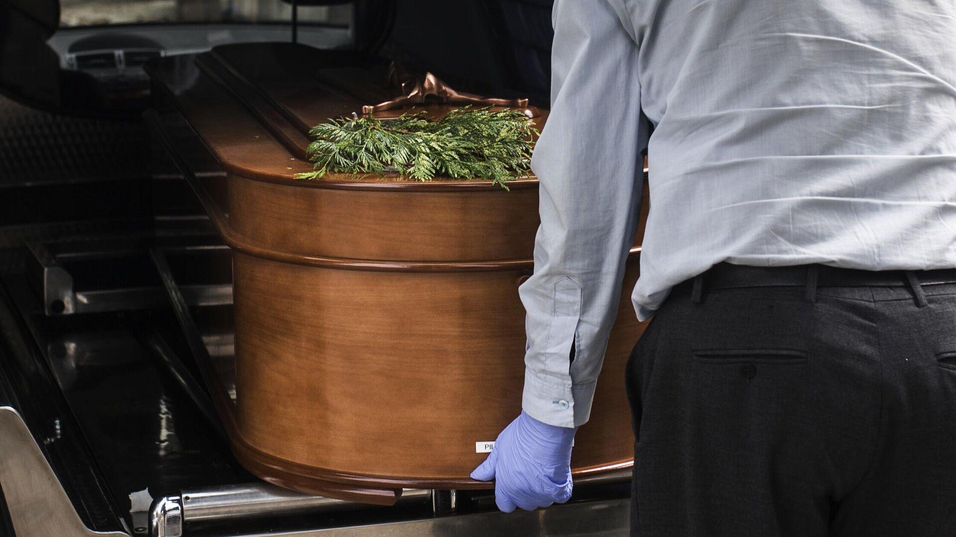 Грузчик достает гроб из катафалка на кладбище Альмудена в Мадриде - РИА Новости, 1920, 11.11.2020