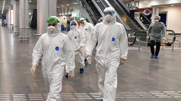 Медицинские работники перед встречей пассажиров, прилетающих из Бангкока в Москву в аэропорту Шереметьево