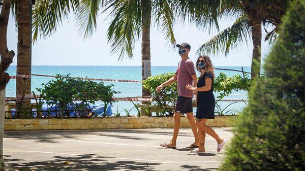 Туристы в защитных масках возле закрытого пляжа в курортном городе Нячанг во Вьетнаме