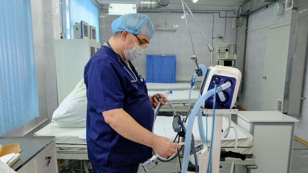 Врач осматривает новые аппараты для ИВЛ