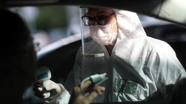 Медсестра измеряет температуру у мужчины в Сан-Паулу, Бразилия
