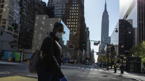 Женщина в медицинской маске пересекает 34-ю улицу в Нью-Йорке