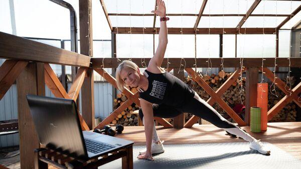 Жительница города Сочи Елена Кузьмина смотрит онлайн-трансляцию занятия по фитнесу у себя дома